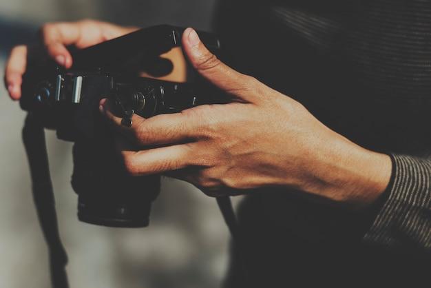 Nahaufnahme von den händen film in der kamera überprüfend