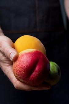 Nahaufnahme von den händen, welche die frischen und rohen früchte anbieten