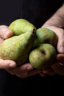 Nahaufnahme von den händen, welche die frischen und rohen grünen birnen anbieten