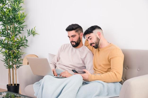 Nahaufnahme von den homosexuellen paaren, die zusammen auf sofa unter verwendung des handys und des laptops sitzen