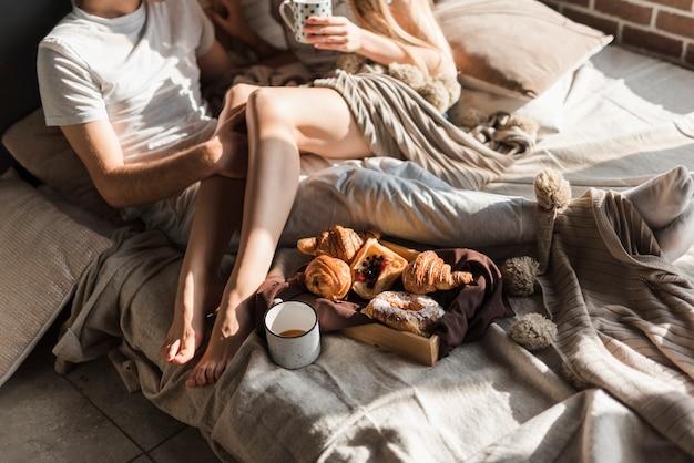 Nahaufnahme von den jungen paaren, die auf bett mit frühstück auf hölzernem behälter sich entspannen
