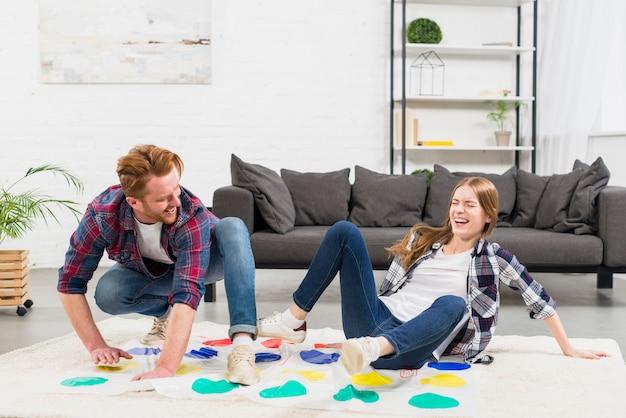 Nahaufnahme von den jungen paaren, die das punktspiel im wohnzimmer spielend genießen