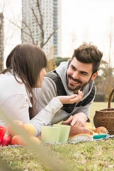 Nahaufnahme von den jungen paaren, die einander im picknick betrachten