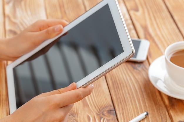 Nahaufnahme von den jungen weiblichen händen, die digitale tablette halten und morgen macchiato trinken.