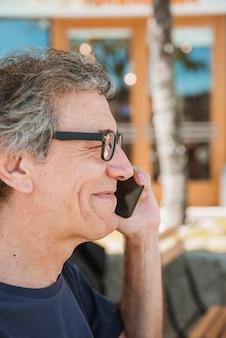 Nahaufnahme von den lächelnden tragenden brillen des älteren mannes, die auf mobiltelefon sprechen