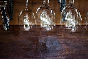 Nahaufnahme von den leeren luxuswein- und champagnergläsern, die oben seite im restaurant hängen.