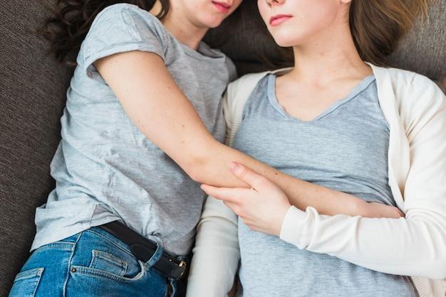 Nahaufnahme von den lesbischen paaren, die zusammen auf sofa liegen