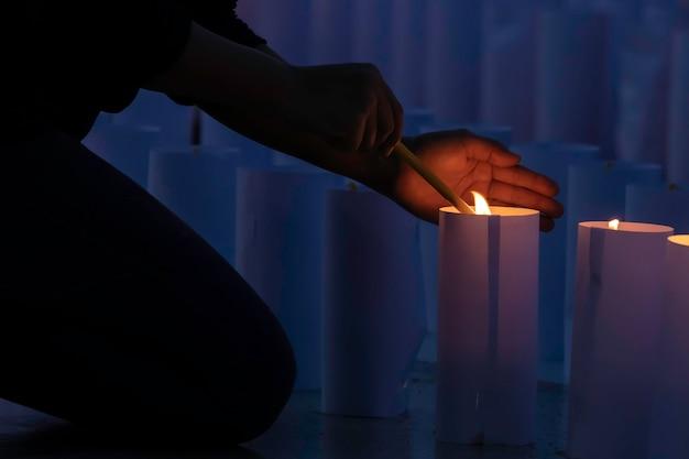 Nahaufnahme von den leuten, die kerzenwache in der dunkelheit ausdrückt und sucht hoffnung halten.