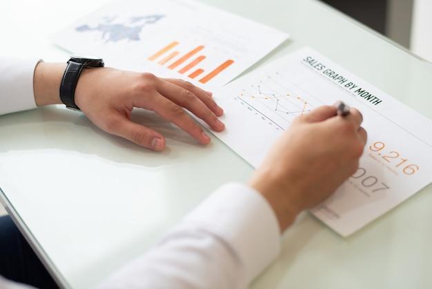 Nahaufnahme von den männlichen händen, die auf papier mit diagrammverkauf schreiben