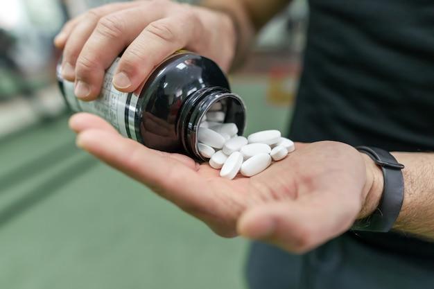 Nahaufnahme von den mannarmen, die sportergänzungen, kapseln, pillen zeigen