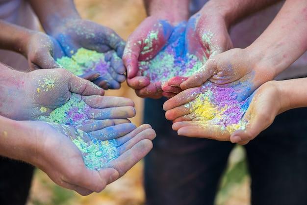 Nahaufnahme von den mehrfachen händen, die pulverfarbe halten