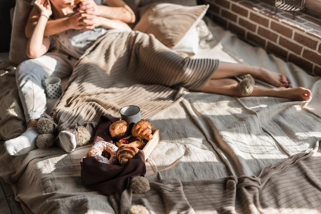 Nahaufnahme von den paaren, die auf bett mit frühstück liegen