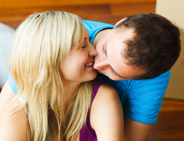 Nahaufnahme von den paaren, die auf neues haus umziehen und küssen