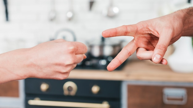 Nahaufnahme von den paaren, die das scherenspiel des scherbenpapiers in der küche spielen