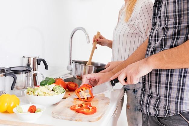 Nahaufnahme von den paaren, die lebensmittel in der küche zubereiten