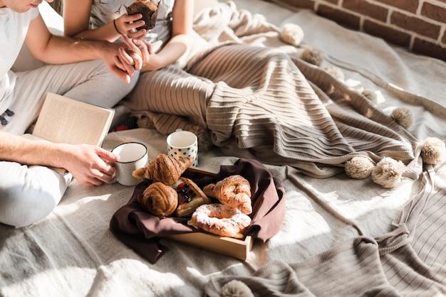 Nahaufnahme von den paaren, die sich die hand halten, die frühstückt