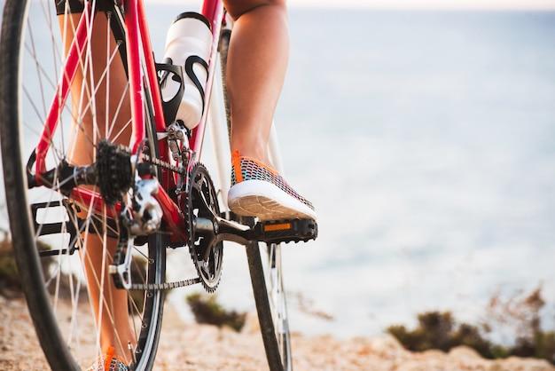 Nahaufnahme von den radfahrerfrauenbeinen, die fahrrad auf spur im freien reiten
