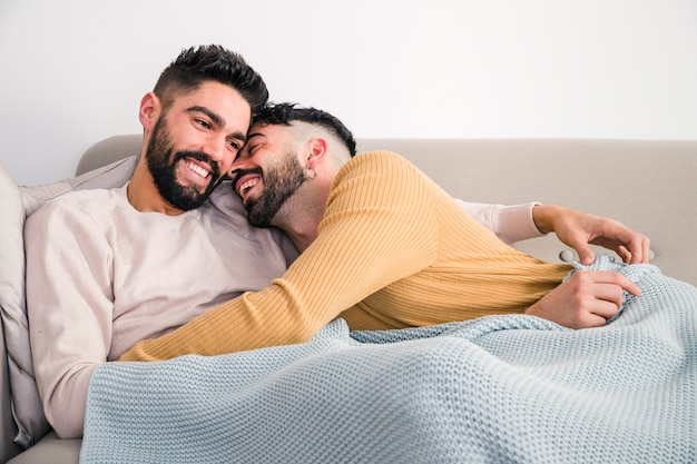 Nahaufnahme von den romantischen jungen homosexuellen paaren, die auf sofa liegen