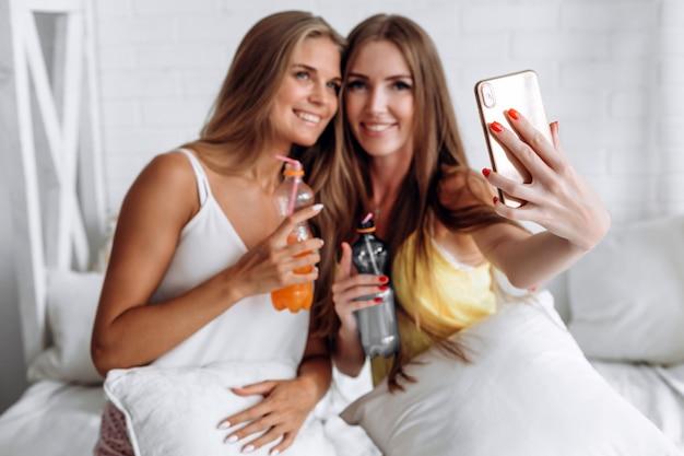 Nahaufnahme von den telefonmädchen, die selfies und das trinken tun