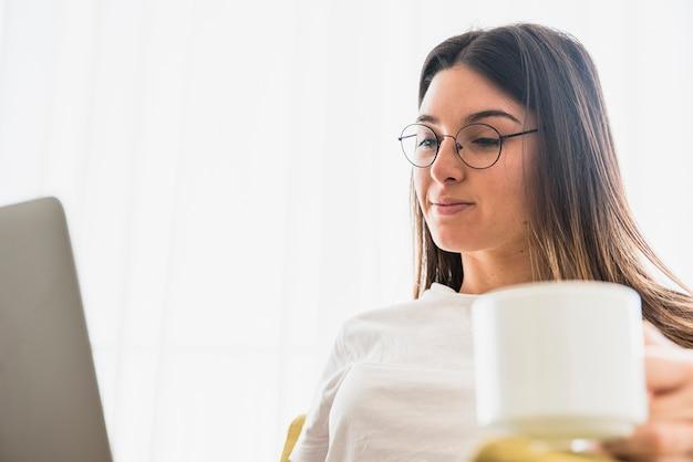 Nahaufnahme von den tragenden brillen der jungen frau, die kaffeetasse unter verwendung des laptops halten