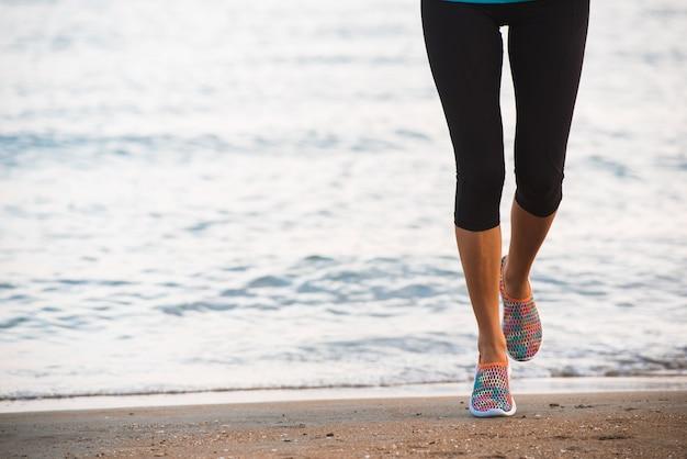 Nahaufnahme von den weiblichen beinen, die auf strand bei sonnenaufgang am morgen laufen