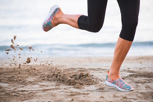 Nahaufnahme von den weiblichen beinen, die auf strand bei sonnenaufgang am morgen mit dem sand in bewegung laufen