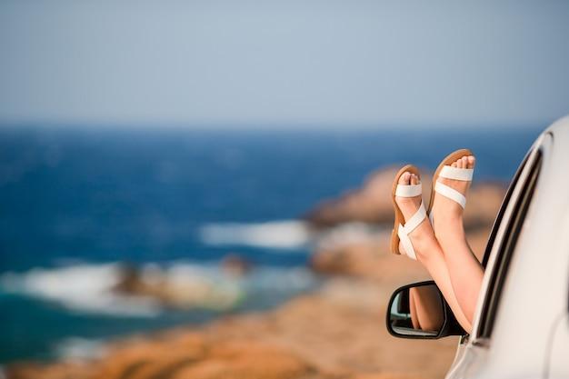 Nahaufnahme von den weiblichen füßen, die vom autofensterhintergrundmeer darstellen