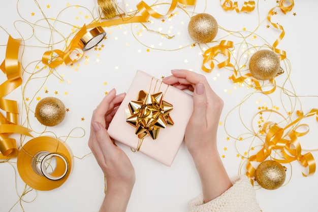 Nahaufnahme von den weiblichen händen, die ein geschenk halten. festlicher weihnachtshintergrund mit copyspace. horizontale ansicht von oben