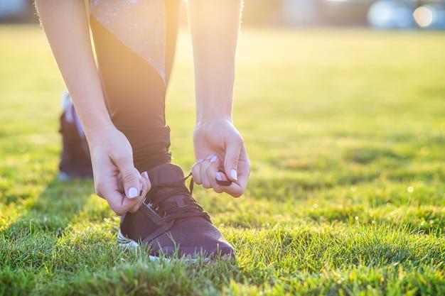 Nahaufnahme von den weiblichen händen, die spitze auf laufschuhen vor praxis binden. läufer, der zum training fertig wird. sport aktives lifestyle-konzept.