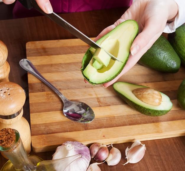 Nahaufnahme von den weiblichen händen kochend mit avocado