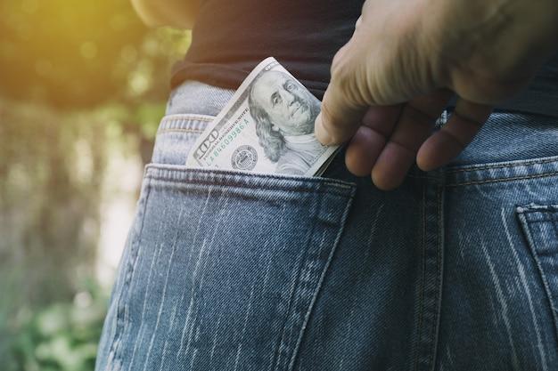 Nahaufnahme von der hand des diebes geld von einer frau stehlend. dieb stehlen geld von bac