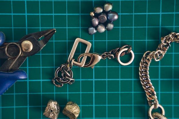 Nahaufnahme von details für die herstellung von handgefertigtem schmuck aus perlen und ketten und werkzeugen, die am arbeitsplatz liegen lying