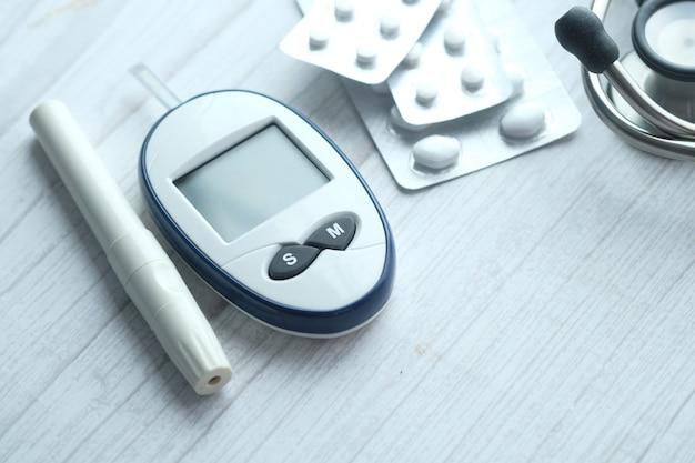 Nahaufnahme von diabetischen messwerkzeugen und pillen auf rosa hintergrund.