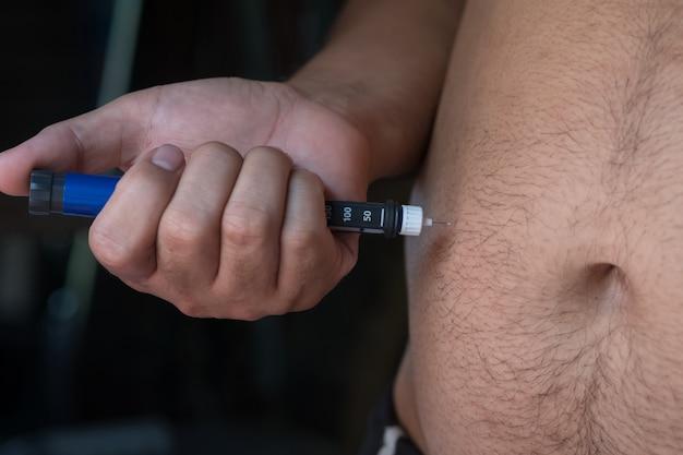 Nahaufnahme von dicken mann hände machen injektion mit insulin-pen