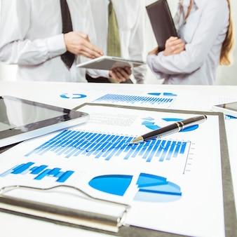 Nahaufnahme von digitalen tablet- und finanzdiagrammen auf dem desktop im hintergrund des geschäftsteams
