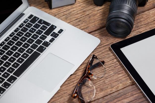 Nahaufnahme von digitalkamera, digitalem tablet, laptop, spektakel auf tisch