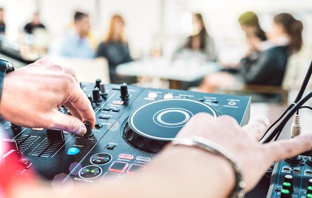 Nahaufnahme von dj, der auf modernem cd-usb-spieler bei sommerstrandparty spielt