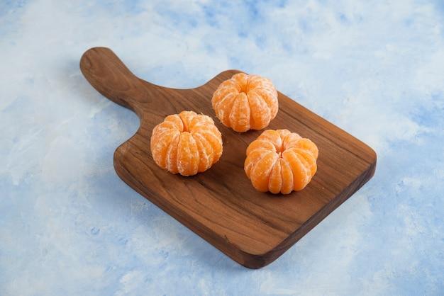 Nahaufnahme von drei geschälten mandarinen