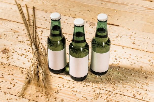 Nahaufnahme von drei grünen alkoholischen flaschen und von ohren weizen auf hölzernem hintergrund