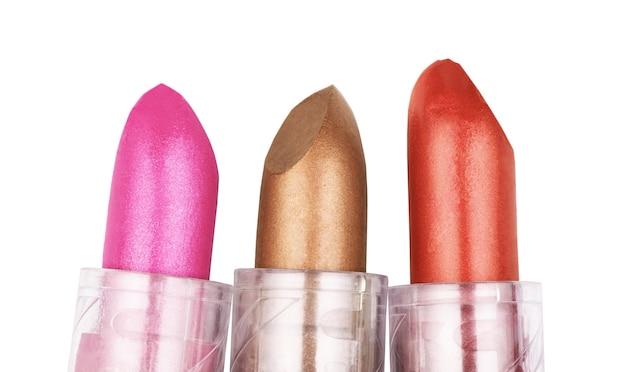 Nahaufnahme von drei lippenstiften in verschiedenen farben, isoliert auf weiss