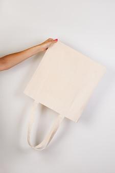Nahaufnahme von ecobag mockup weibliche hand hält umgekehrten weißen ecobag aus recycelten materialien auf weißem...