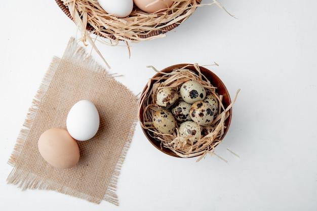 Nahaufnahme von eiern auf sackleinen und schüssel von eiern im nest auf weißem hintergrund mit kopienraum