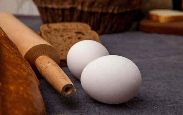 Nahaufnahme von eiern mit nudelholz auf kastanienbrauner oberfläche