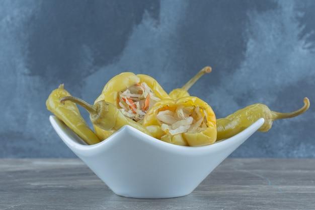 Nahaufnahme von eingelegten grünen paprika gefüllt mit geschnittenem kohl in weiße schüssel