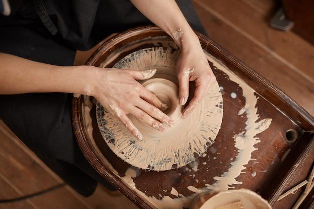Nahaufnahme von eleganten weiblichen händen, die ton auf der töpferscheibe in der werkstatt formen, während sie kunst und kunsthandwerk genießen, raum kopieren