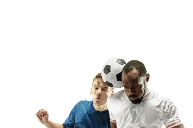 Nahaufnahme von emotionalen männern, die fußball spielen und den ball mit dem kopf auf isoliert auf weißer wand schlagen. fußball, sport, gesichtsausdruck, konzept der menschlichen emotionen. exemplar. kampf ums tor.