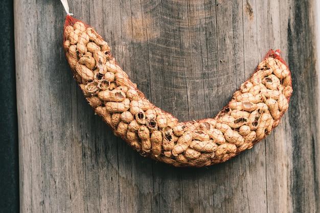 Nahaufnahme von erdnüssen in einem roten netz, das auf dem holz unter den lichtern hängt