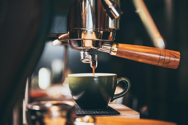 Nahaufnahme von espresso, der aus kaffeemaschine gießt. professionelle kaffeezubereitung