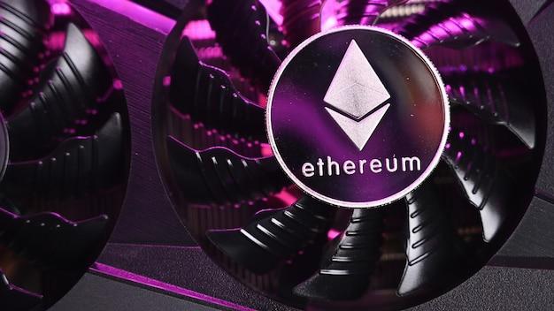 Nahaufnahme von ethereum-münze auf einer schwarzen grafikkarte, die von violettem licht beleuchtet wird. ethereum-mining-konzept.