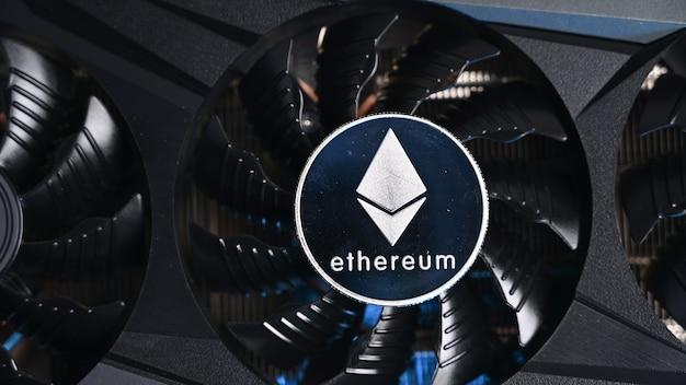 Nahaufnahme von ethereum-münze auf einer schwarzen grafikkarte. kryptowährungs-geschäftsgerät. ethereum-miner.